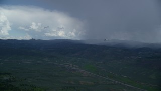 AX140_048 - 6K stock footage aerial video track distant Tecnam P2006T and Cessna near rainstorm and Highway 6, Wasatch Range, Utah