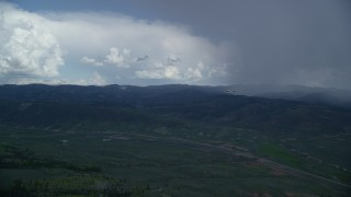 AX140_049 - 6K stock footage aerial video of a Tecnam P2006T and Cessna flying by rainstorm and Highway 6, Wasatch Range, Utah