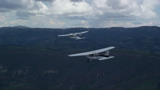 AX140_052 - 6K stock footage aerial video of tracking Tecnam P2006T from behind Cessna flying by mountains, Wasatch Range, Utah