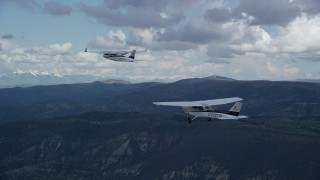 AX140_053 - 6K stock footage aerial video of Tecnam P2006T leading a Cessna by mountains, Wasatch Range, Utah