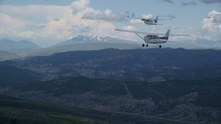 AX140_054 - 6K stock footage aerial video fly behind Cessna following Tecnam P2006T flying by mountains, Wasatch Range, Utah