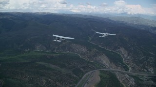 AX140_065 - 6K stock footage aerial video of a Tecnam P2006T leading a Cessna over mountains and Highway 6, Wasatch Range, Utah