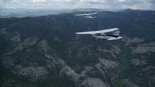AX140_071 - 6K stock footage aerial video of flying near a Cessna being led over mountains by Tecnam P2006T, Wasatch Range, Utah
