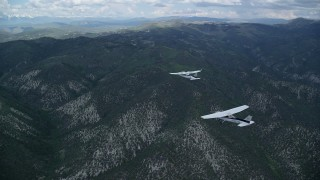 AX140_073 - 6K stock footage aerial video of tracking a Cessna following a Tecnam P2006T across Wasatch Range, Utah