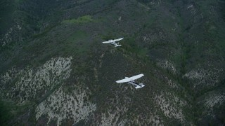 AX140_074 - 6K stock footage aerial video of a bird's eye of a Cessna following a Tecnam P2006T over the Wasatch Range, Utah
