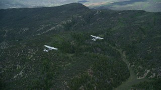 AX140_075 - 6K stock footage aerial video of a Tecnam P2006T leading a Cessna over Wasatch Range, Utah