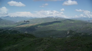 AX140_077 - 6K stock footage aerial video view of Tecnam P2006T leading a Cessna over the Wasatch Range, Utah