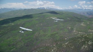 AX140_081 - 6K stock footage aerial video of flying around a Tecnam P2006T leading a Cessna over mountains, Wasatch Range, Utah