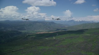 AX140_083 - 6K stock footage aerial video of aTecnam P2006T and Cessna over mountains near winding road, Wasatch Range, Utah