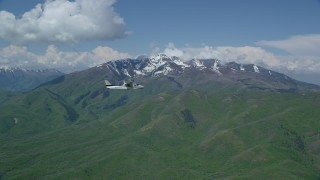 AX140_108 - 6K stock footage aerial video of a Tecnam P2006T in flight near near snowy Wasatch Range peak, Utah