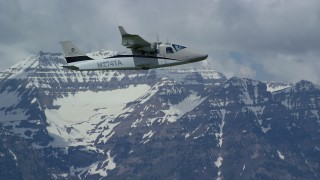 AX140_160 - Aerial stock footage of Tracking a Tecnam P2006T flying by snow-capped Mount Timpanogos, Utah