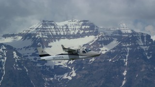 AX140_161 - Aerial stock footage of Tracking a Tecnam P2006T flying by snow-capped Mount Timpanogos, Utah