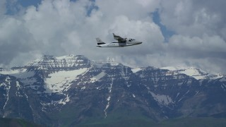 AX140_162 - Aerial stock footage of Tracking a Tecnam P2006T flying by snow-capped Mount Timpanogos, Utah