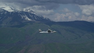 AX140_163 - Aerial stock footage of Tracking a Tecnam P2006T flying by snow-capped Mount Timpanogos, Utah