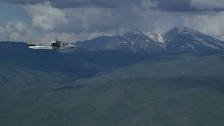 AX140_164 - Aerial stock footage of Track Tecnam P2006T by White Baldy, reveal snowy Mount Timpanogos, Utah
