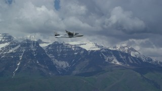 AX140_165 - Aerial stock footage of Tracking Tecnam P2006T flying by snow-capped Mount Timpanogos, Utah