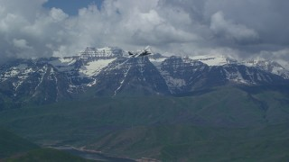 AX140_168 - Aerial stock footage of Tracking Tecnam P2006T briefly by snow-capped Mount Timpanogos, Utah