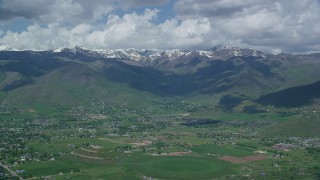 AX140_179 - 6K stock footage aerial video of a wide view of snowy peaks from small town of Midway, Wasatch Range, Utah