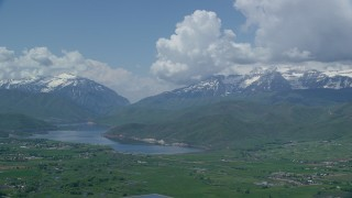 AX140_181 - 6K stock footage aerial video of snowy Mount Timpanogos and Deer Creek Reservoir, seen from Midway, Utah
