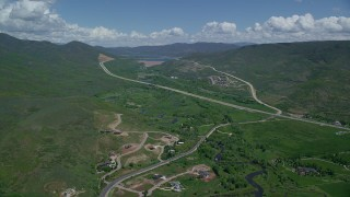 AX140_185 - 6K stock footage aerial video of flying by Highway 40 through green mountain foothills and homes, Heber City, Utah