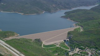 AX140_191 - 6K stock footage aerial video of a dam surrounded by green hills, reveal the highway, Jordanelle Dam, Utah