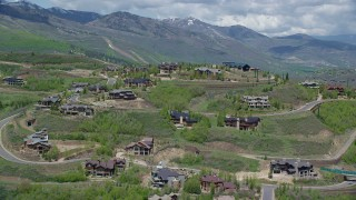 AX140_197 - 6K stock footage aerial video of flying by upscale mountaintop homes, Deer Valley, Utah