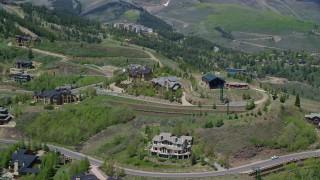 AX140_198 - 6K stock footage aerial video of passing by upscale mountaintop homes, Deer Valley, Utah