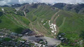 AX140_204 - 6K stock footage aerial video of Park City Mountain Resort, green slopes and distant snowy peaks, Park City, Utah