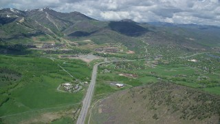 AX140_207 - 6K stock footage aerial video follow State Route 224 to approach Canyons Resort and Park City neighborhoods, Utah