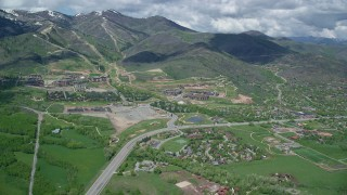 AX140_208 - 6K stock footage aerial video of flying by Canyons Resort near snowy mountain peaks, Park City, Utah