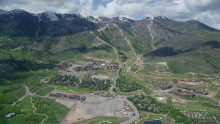AX140_209 - 6K stock footage aerial video of Canyons Resort, with view of snowy mountain peaks, Park City, Utah