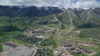 AX140_210 - 6K stock footage aerial video orbit Canyons Resort and snowy mountain peaks, Park City, Utah