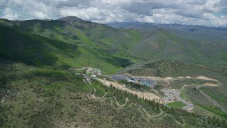 AX140_212 - 6K stock footage aerial video of approaching Olympic ski jumps at the base of green mountains, Utah Olympic Park