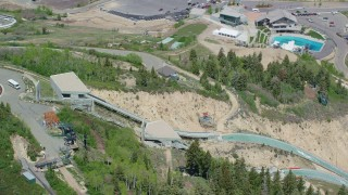 AX140_220 - 6K stock footage aerial video orbit the ski jumps, reveal the pool at Utah Olympic Park