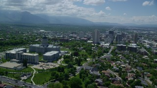 AX140_256 - 6K stock footage aerial video of passing the Utah State Capitol with view of Downtown Salt Lake City, Utah