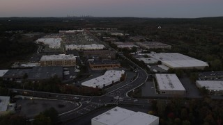 AX141_001 - 6K stock footage aerial video of a strip mall, warehouse buildings, University Avenue, Westwood, Massachusetts, twilight