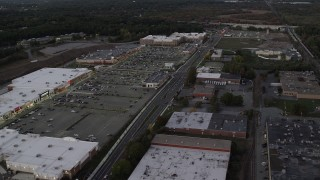 AX141_002 - 6K stock footage aerial video flying by a strip mall, panning left, Westwood, Massachusetts, twilight