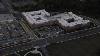 AX141_003 - 6K stock footage aerial video flying by a large apartment building, Westwood, Massachusetts, twilight