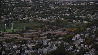 AX141_007 - 6K stock footage aerial video approaching apartment buildings, Dorchester Center, Boston, Massachusetts, twilight