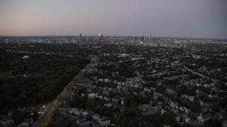 AX141_009 - 6K stock footage aerial video flying over suburban neighborhood, Dorchester, approach Downtown Boston, Massachusetts, twilight