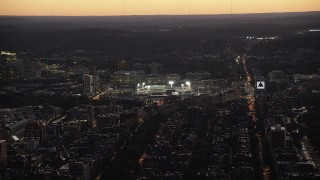 AX141_029 - 6K stock footage aerial video flying by Fenway Park under lights, Boston, Massachusetts, twilight