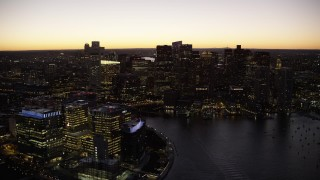 AX141_042 - 6K stock footage aerial video flying by skyline, boats in the harbor, Downtown Boston, Massachusetts, twilight