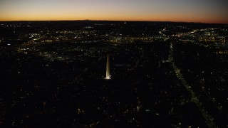 AX141_069 - 6K stock footage aerial video orbiting Bunker Hill Monument, neighborhoods, Charlestown, Massachusetts, twilight