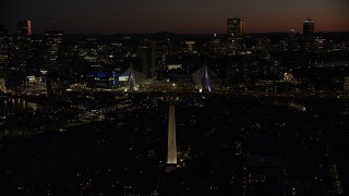 AX141_071 - 6K stock footage aerial video orbiting Bunker Hill Monument, Zakim Bridge, downtown skyline, Charlestown, Massachusetts, night