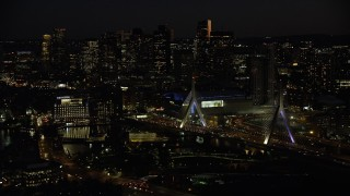 AX141_073 - 6K stock footage aerial video approaching Zakim Bridge, TD Garden, Avalon North Station, Downtown Boston, Massachusetts, night