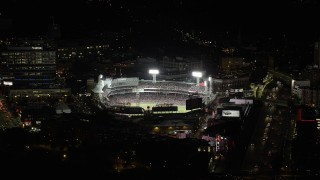 AX141_080 - 6K stock footage aerial video flying by Prudential Tower, reveal baseball game, Fenway Park, Boston, Massachusetts, night