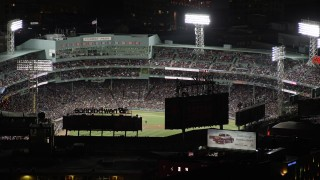 AX141_082 - 6K stock footage aerial video flying by baseball game at Fenway Park, Boston, Massachusetts, night
