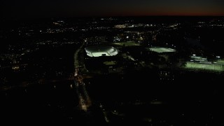 AX141_105 - 6K stock footage aerial video approaching Harvard Stadium, tilt down, Harvard University, Massachusetts, night