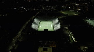 AX141_106 - 6K stock footage aerial video approaching a well-lit Harvard Stadium, tilt down, Harvard University, Massachusetts, night