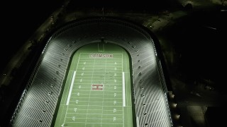 AX141_107 - 6K stock footage aerial video of a bird's eye view over a well-lit Harvard Stadium, Harvard University, Massachusetts, night